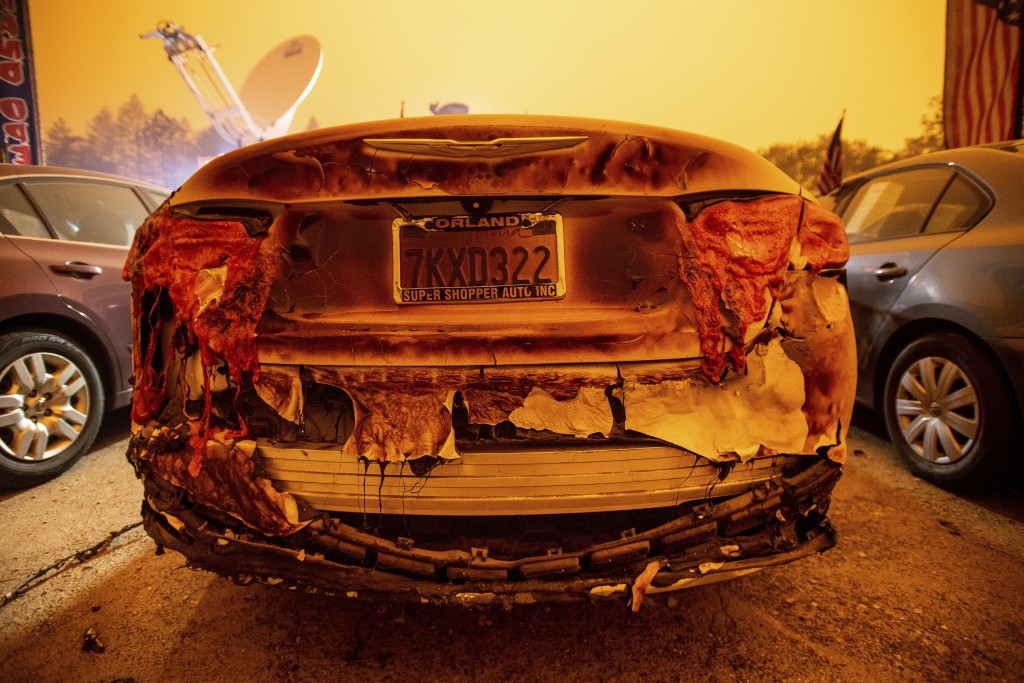 A scorched vehicle sits parked at a used car dealership after a wildfire burned through Paradise, Calif., on Friday, Nov. 9, 2018. (AP Photo/Noah Berg