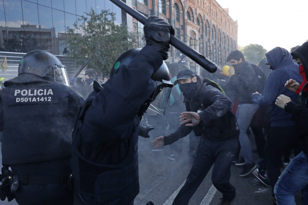 Police charge against protesters during a demonstration by CDR (Committees for the Defense of the Republic) in Barcelona, Spain, Saturday, Nov. 10, 20