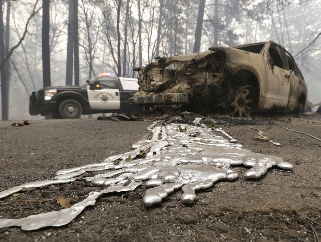 A California Highway Patrol vehicle passes a vehicle Friday, Nov. 9, 2018, destroyed by a wildfire in Paradise, Calif. The wind-whipped fires have des