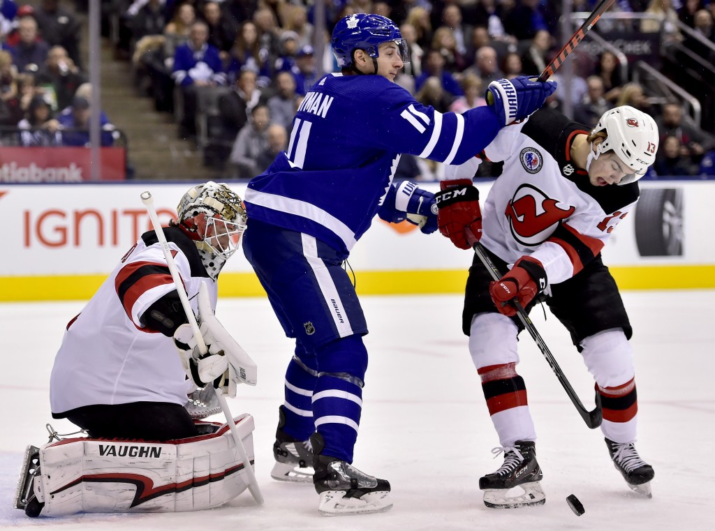 Toronto Maple Leafs left wing Zach Hyman (11) challenges New Jersey Devils center Nico Hischier (13) for the puck as Devils goaltender Keith Kinkaid (