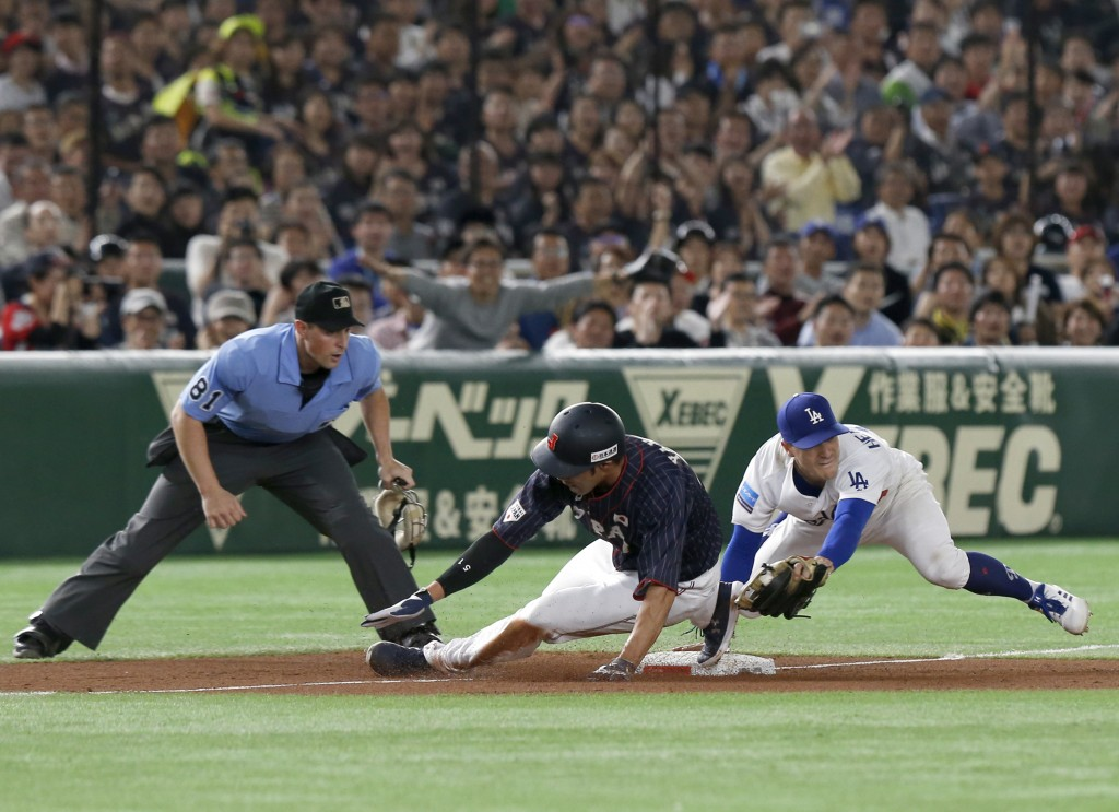 MLB All-Star third baseman Enrique Hernandez, right, of the Los Angeles Dodgers cannot tag All Japan's Seiji Uebayashi sliding into third in the fifth