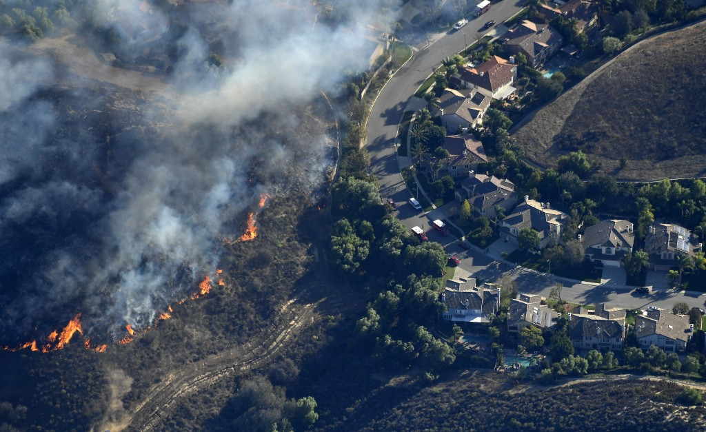 Fires burn toward homes Friday, Nov. 9, 2018, as seen from a helicopter over the Calabasas section of Los Angeles. Flames driven by powerful winds tor