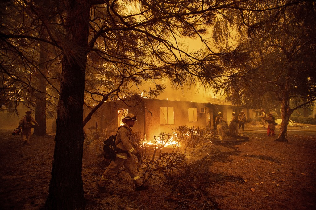 Firefighters work to keep flames from spreading through the Shadowbrook apartment complex as a wildfire burns through Paradise, Calif., on Friday, Nov