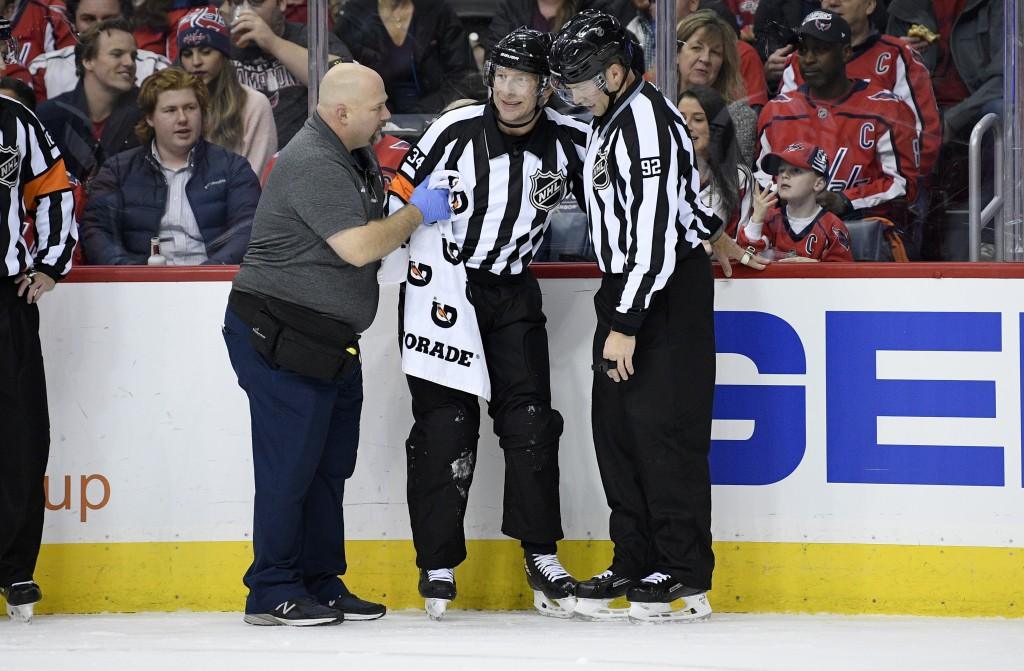 Referee Brad Meier (34) is tended to by a trainer and linesman Mark Shewchyk (92) after he was injured during the first period of an NHL hockey game b