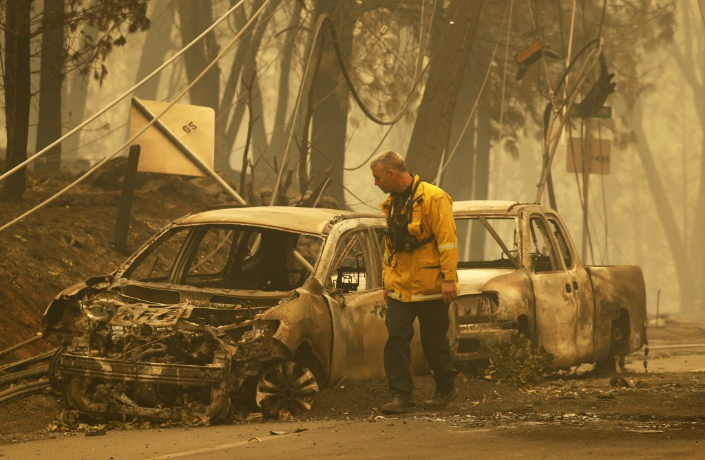 A Sonoma Valley firefighter inspects burned out cars to make sure they are clear of human remains, Friday, Nov. 9, 2018, in Paradise, Calif. (AP Photo
