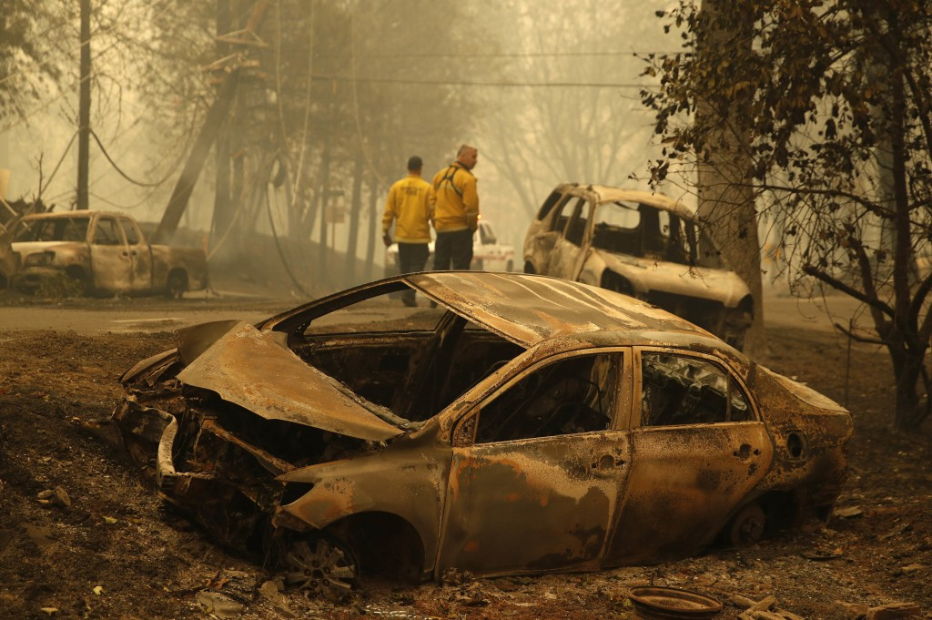 Sonoma Valley firefighters inspect burned out cars to make sure they are clear of human remains following a fire through a neighborhood, Friday, Nov. ...