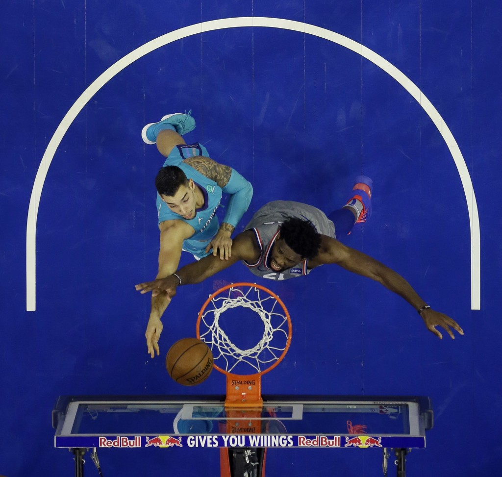 Charlotte Hornets' Willy Hernangomez, left, goes up for a shot against Philadelphia 76ers' Joel Embiid during the second half of an NBA basketball gam