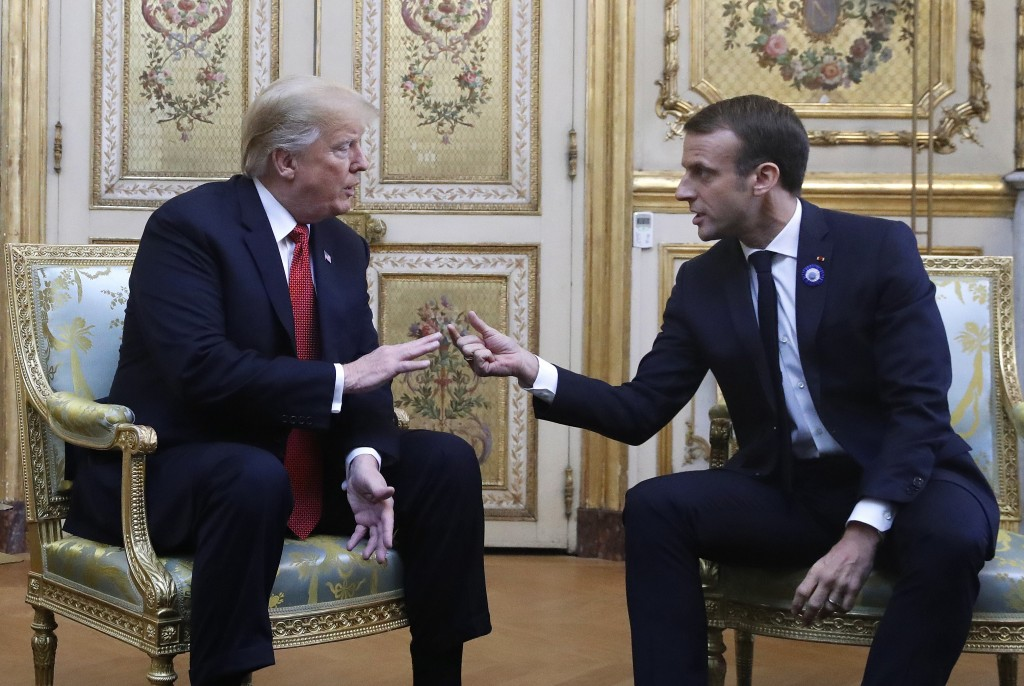 President Donald Trump and French President Emmanuel Macron gesture during their meeting inside the Elysee Palace in Paris Saturday Nov. 10, 2018. Tru