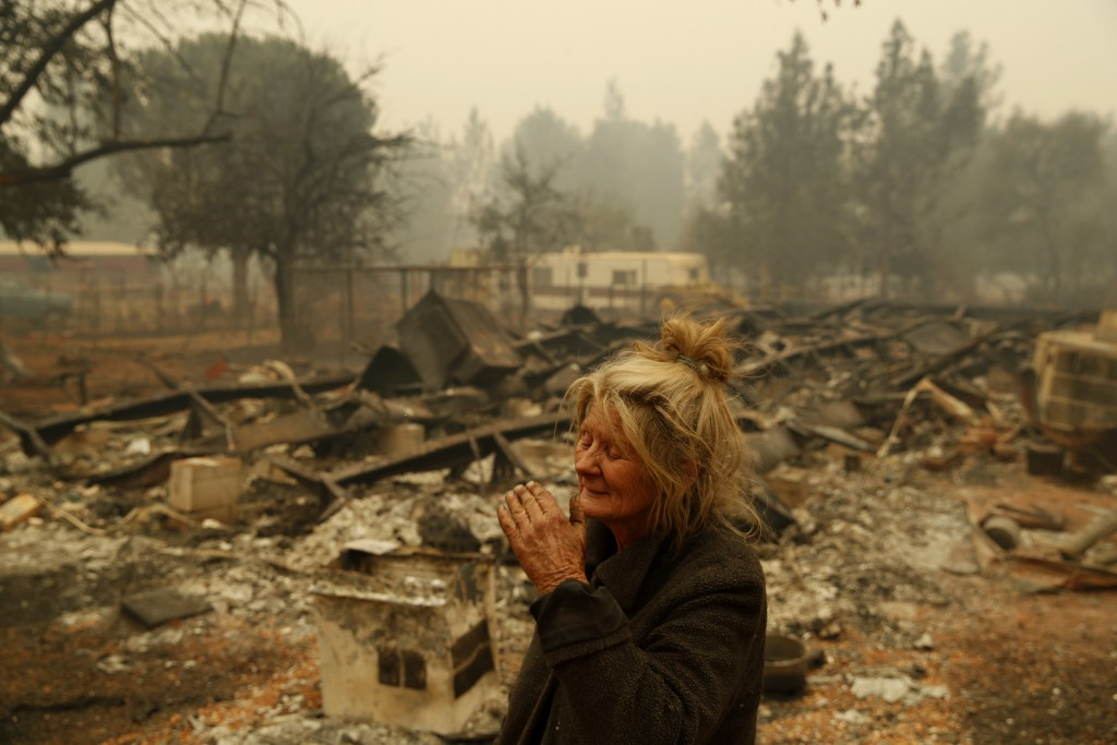 """Cathy Fallon reacts as she stands near the charred remains of her home, Friday, Nov. 9, 2018, in Paradise, Calif. """"I'll be darned if I'm going to let"""
