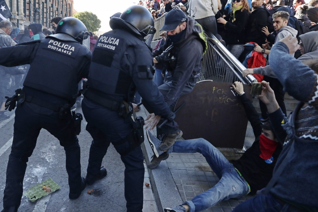 Police charge react with protesters during a demonstration by CDR (Committees for the Defense of the Republic) in Barcelona, Spain, Saturday, Nov. 10,