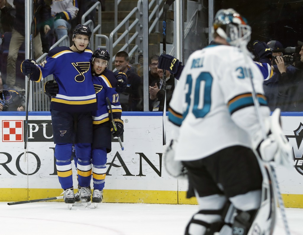 St. Louis Blues' Jaden Schwartz, center, is congratulated by Colton Parayko, left, as he celebrates after scoring past San Jose Sharks goaltender Aaro...