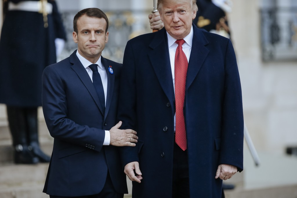 French President Emmanuel Macron, left, poses with President Donald Trump prior to their meeting at the Elysee presidential palace, in Paris, Saturday