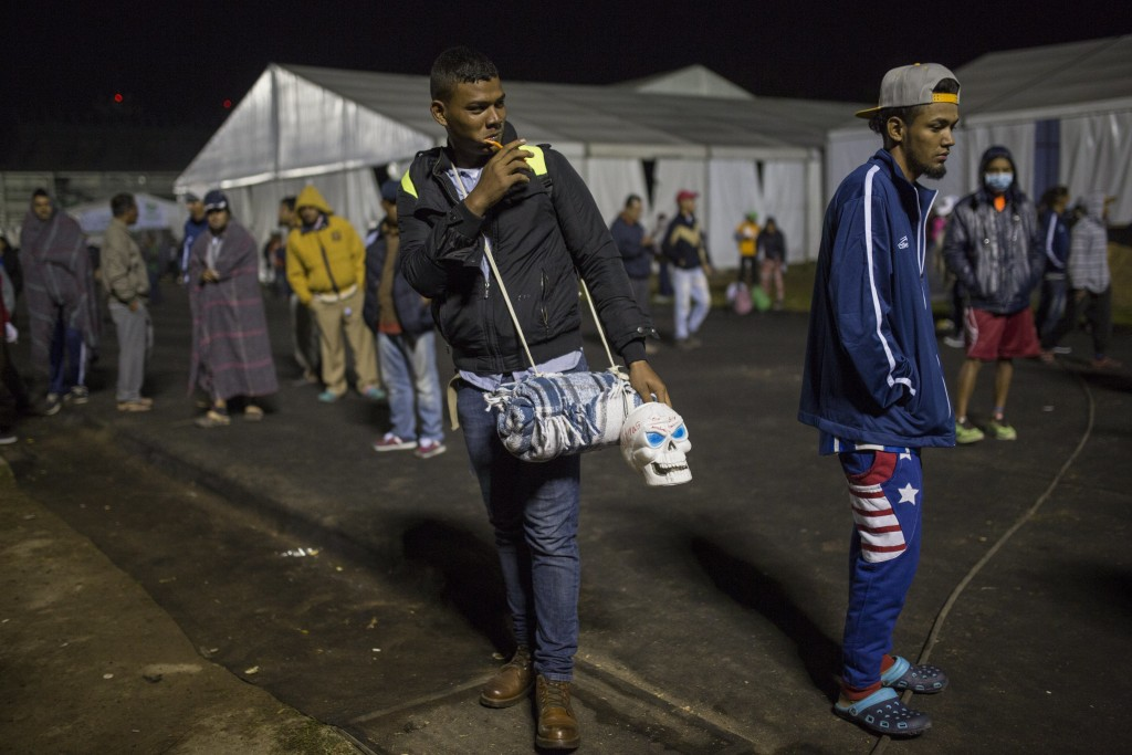 A Central American migrant prepares to leave the temporary shelter in the Jesus Martinez stadium, in Mexico City, Friday, Nov. 9, 2018. A group of 500