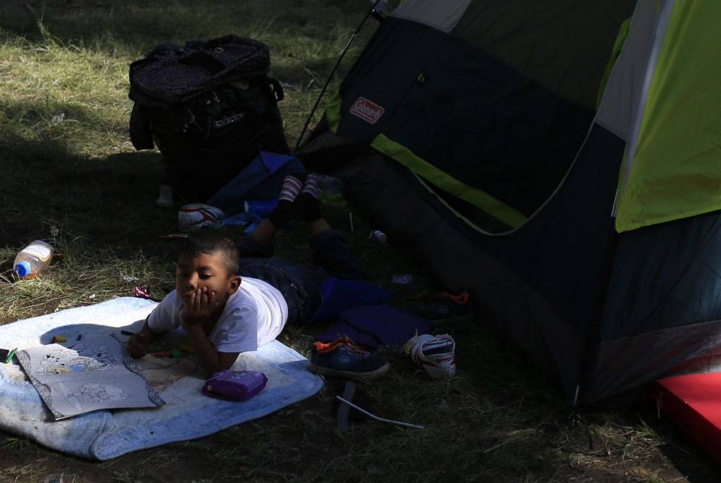 A boy lies with a coloring book outside a tent inside the sports complex where thousands of migrants have been camped out for several days in Mexico C