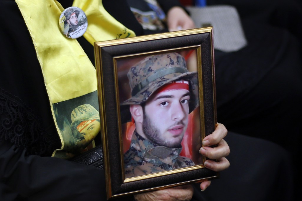 A supporter of the Iranian-backed Hezbollah group carries pictures of her son who died fighting with Hezbollah as they listen to a speech of Hezbollah