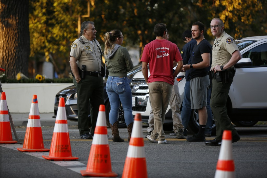 Thousand Oaks residents await to claim their vehicles as FBI agents verify vehicle registrations of autos parked in the lot of the Borderline Bar & Gr