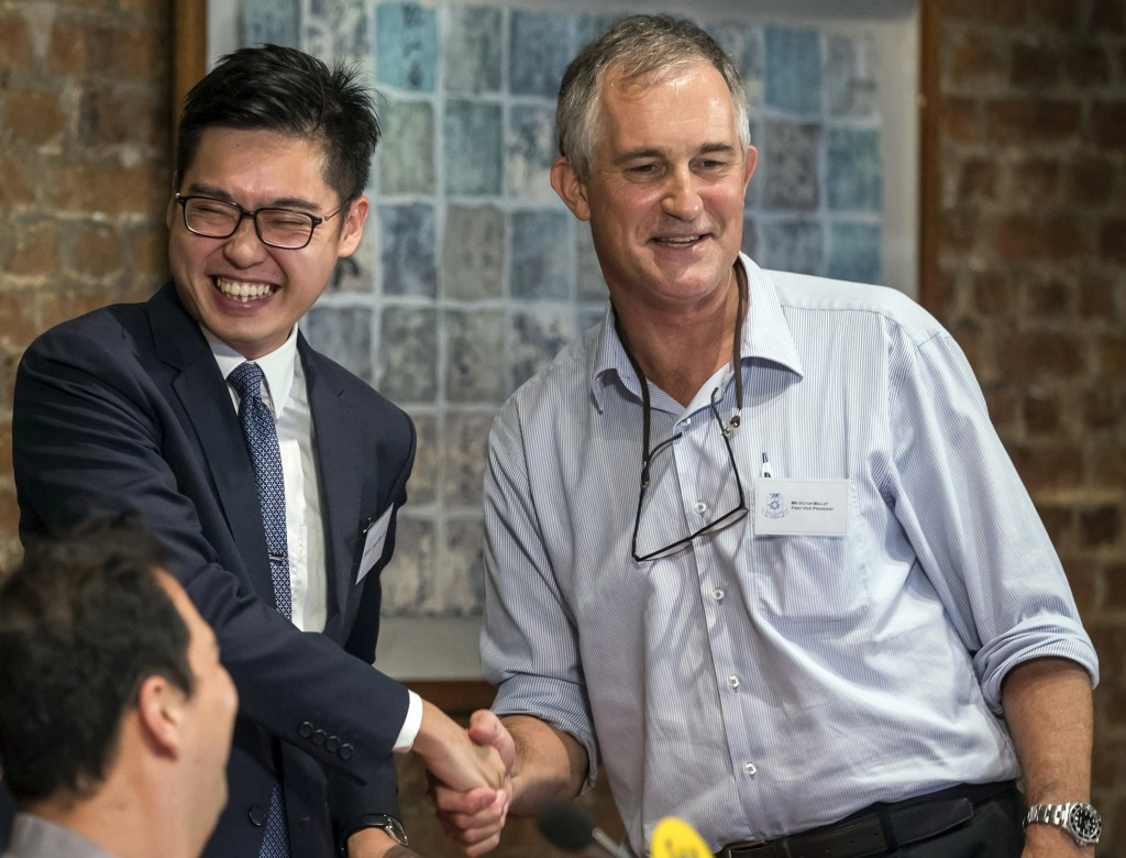 FILE - In this Aug. 14, 2018, file photo, The Financial Times Asia news editor, Victor Mallet, right, shakes hands with Andy Chan, founder of the Hong