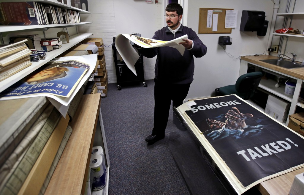 Brian Sylvester, director of the Rochester Public Library, carries an original war poster at the library's archive in Rochester, N.H., Thursday, Nov.