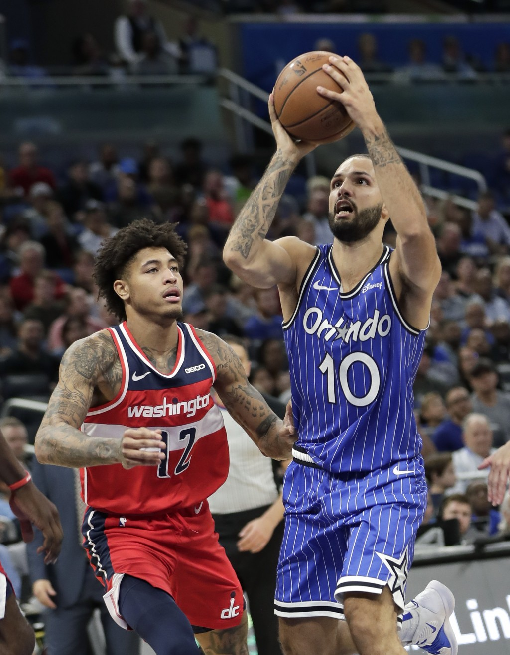 Orlando Magic guard Evan Fournier (10) goes up for a shot against Washington Wizards' Kelly Oubre Jr. (12) during the second half of an NBA basketball