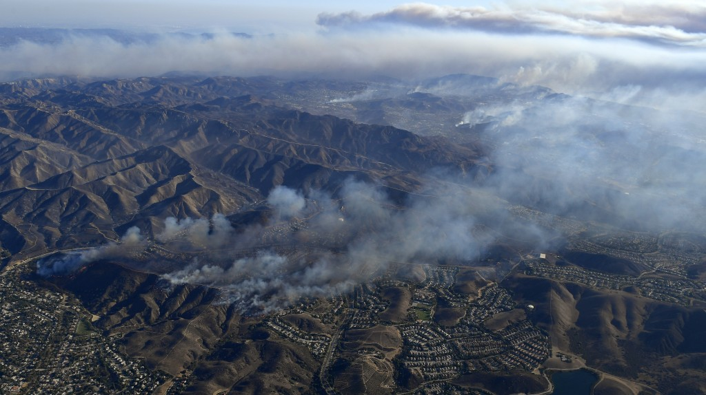 Fires burn toward the Pacific Ocean Friday, Nov. 9, 2018, as seen from a helicopter over Simi Valley, Calif. Flames driven by powerful winds torched d