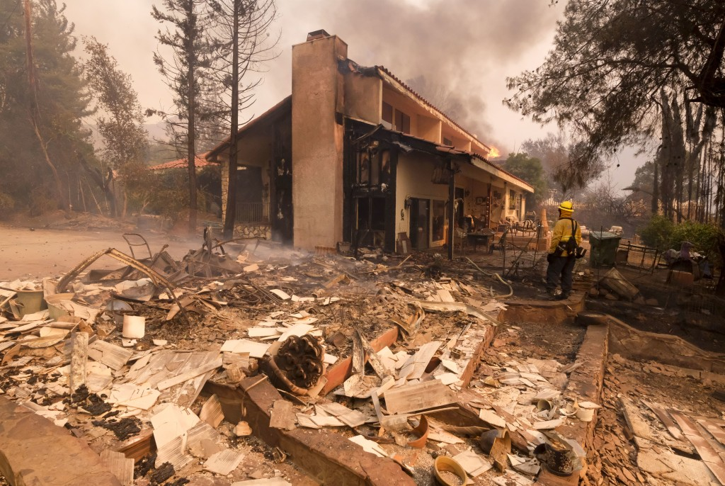 A firefighter keeps watch as the charred remains of a burned out home are seen during the Woolsey Fire in Malibu, Calif., Friday, Nov. 9, 2018. (AP Ph