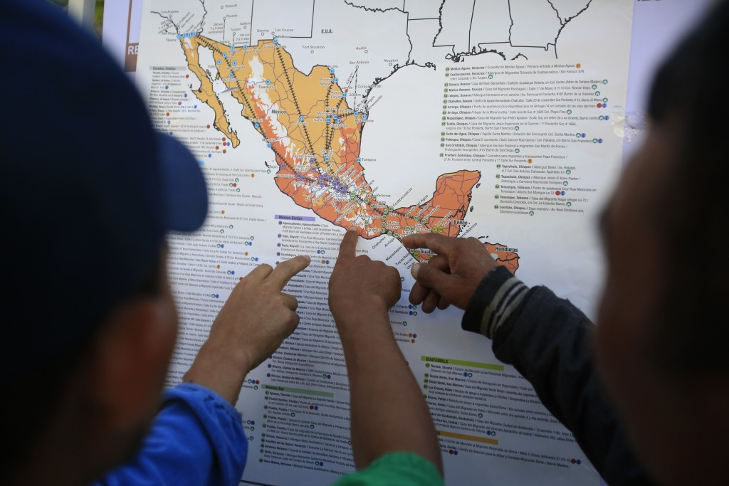 Migrants discuss their journey using a map posted inside the sports complex where thousands of migrants have been camped out for several days in Mexic