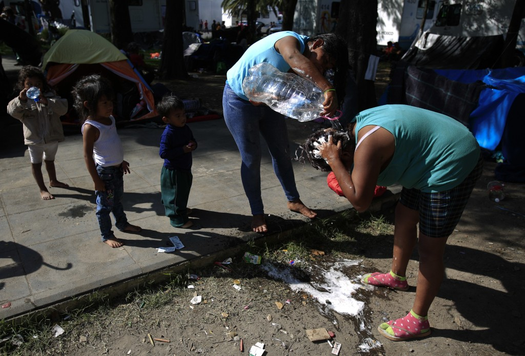 Women use water from a bottle to wash their hair in a sports complex where thousands of migrants have been camped out for several days in Mexico City,