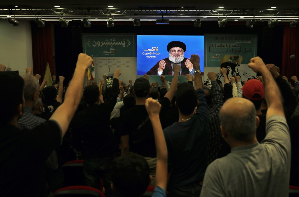 Supporter of the Iranian-backed Hezbollah group raise their fists and cheer as they listen to a speech of Hezbollah leader Sayyed Hassan Nasrallah, vi