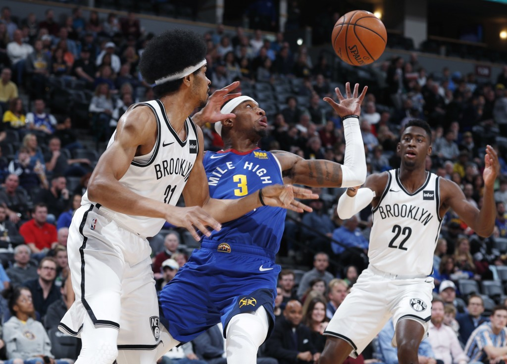 Denver Nuggets forward Torrey Craig, center, tries to pull in a loose ball between Brooklyn Nets center Jarrett Allen, left, and guard Caris LeVert in