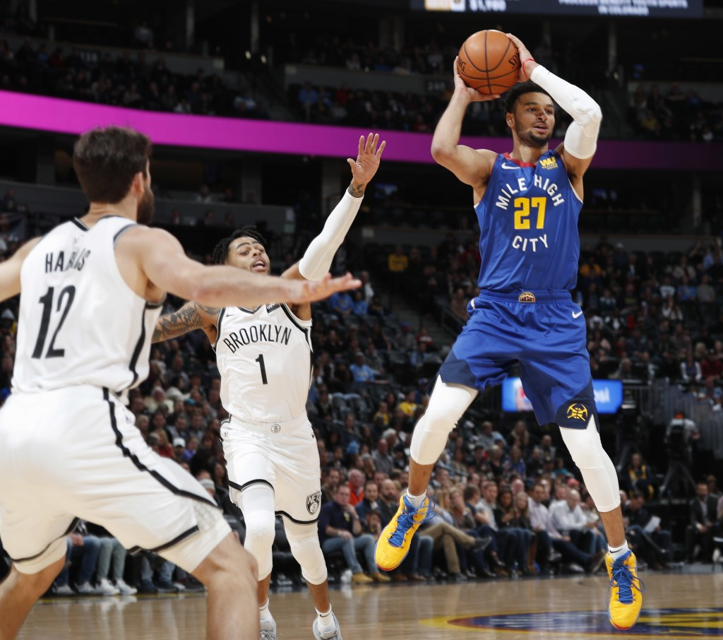 Denver Nuggets guard Jamal Murray, right, looks to pass the ball as Brooklyn Nets forward Joe Harris, left, and guard D'Angelo Russell defend in the f