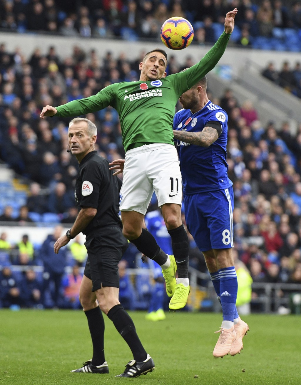 Brighton & Hove Albion's Anthony Knockaert and Cardiff City's Joe Ralls,, right, leap for the ball during the English Premier League soccer match betw