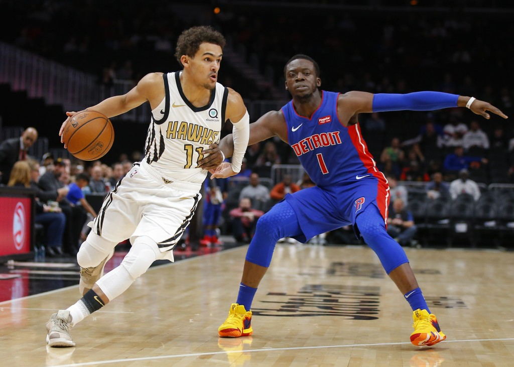 Atlanta Hawks guard Trae Young (11) drives to the basket as Detroit Pistons guard Reggie Jackson (1) defends during the first half of an NBA basketbal