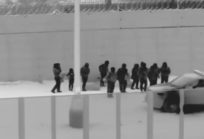 This image from video provided by the Yuma Sector Border Patrol shows a group of migrants who crawled through a hole that had been dug under the U.S.-