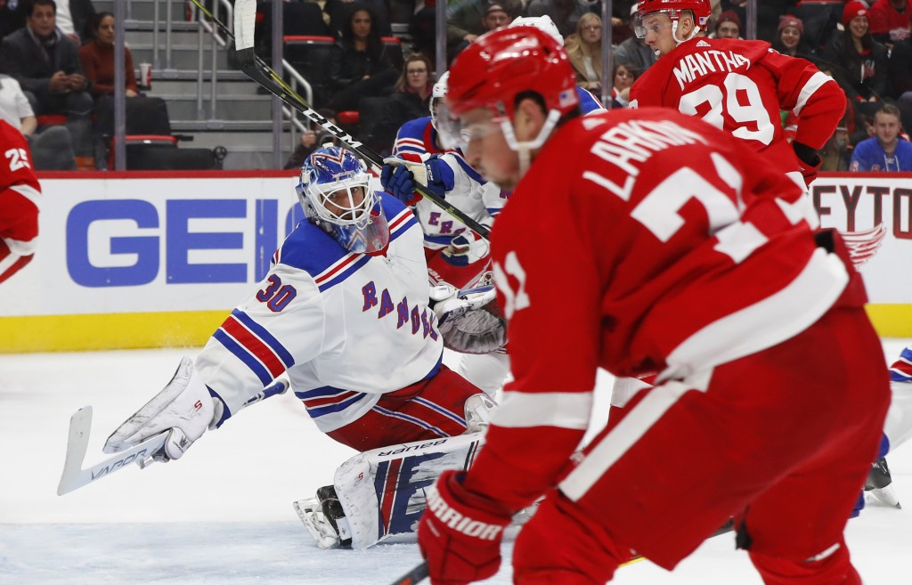 New York Rangers goalie Henrik Lundqvist (30) reaches to block a shot by Detroit Red Wings' Dylan Larkin in the second period of an NHL hockey game in
