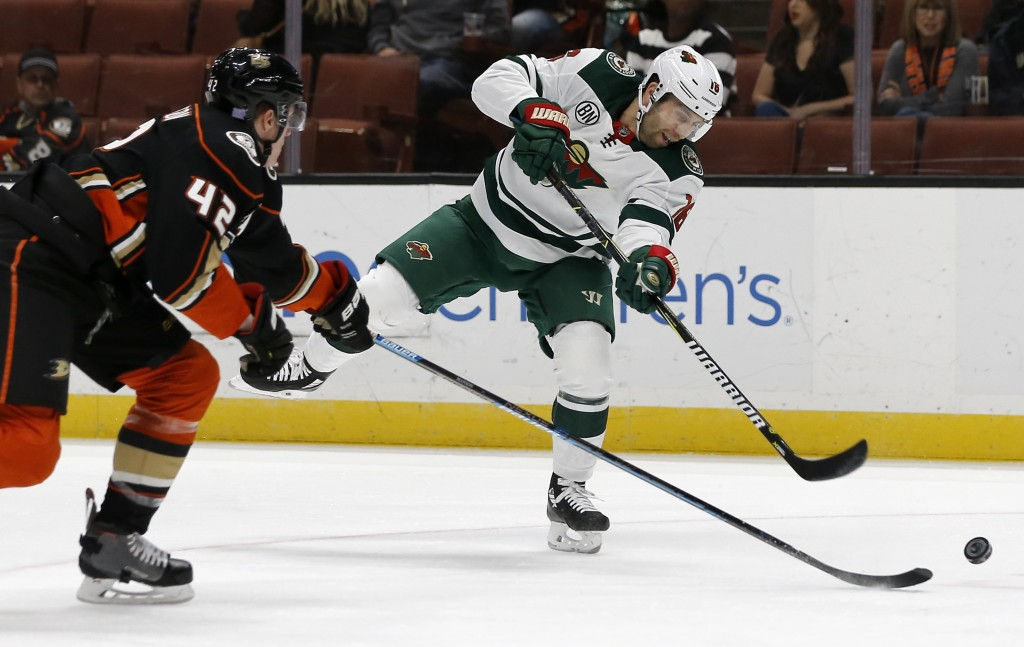 Minnesota Wild left wing Jason Zucker, right, shoots as Anaheim Ducks defenseman Josh Manson, left, defends during the first period of an NHL hockey g