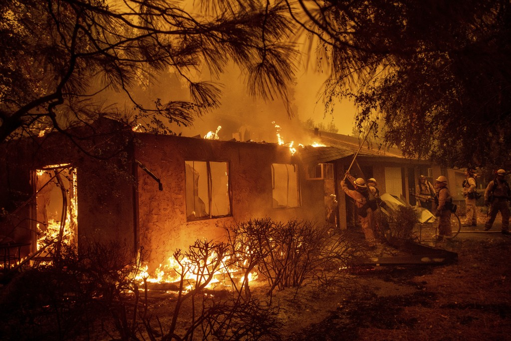 Firefighters work to keep flames from spreading through the Shadowbrook apartment complex as a wildfire burns through Paradise, Calif., on Friday, Nov...