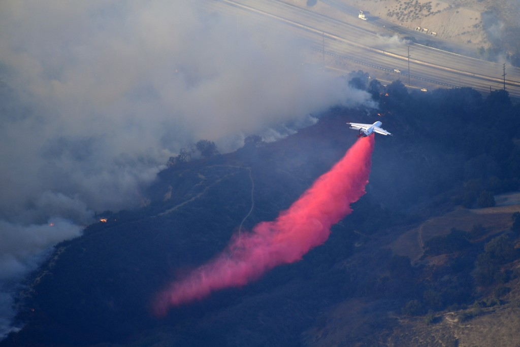 An air tanker drops flame retardant to protect homes as fires burn Friday, Nov. 9, 2018, as seen from a helicopter over the Calabasas section of Los A