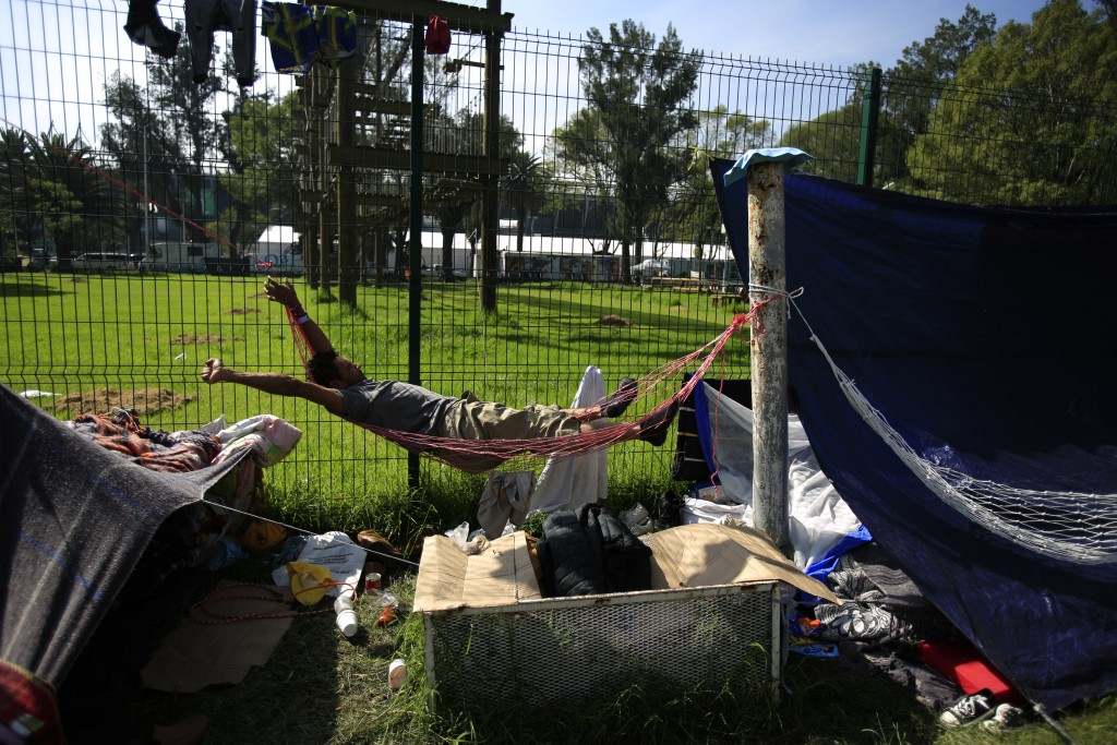 A man stretches as he awakens in a hammock at the sports complex where thousands of migrants have been camped out for several days in Mexico City, Fri