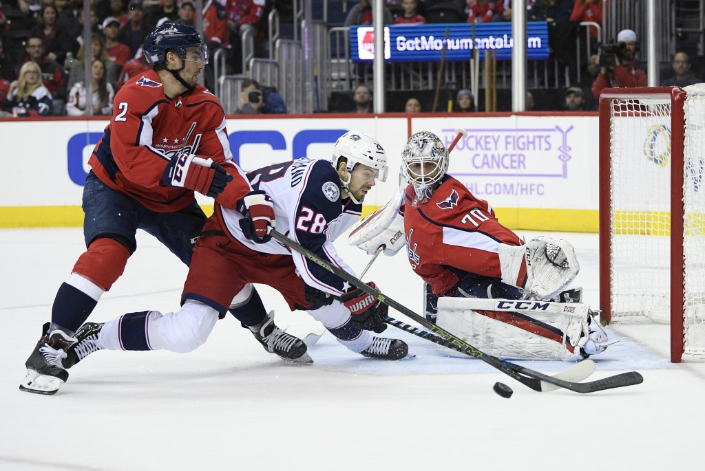 Columbus Blue Jackets right wing Oliver Bjorkstrand (28), of Denmark, battles for the puck against Washington Capitals defenseman Matt Niskanen (2) an