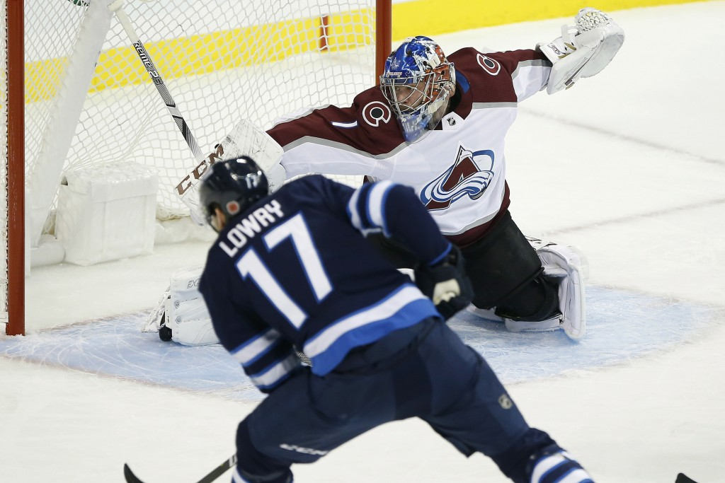 Winnipeg Jets' Adam Lowry's (17) shot is saved by Colorado Avalanche goaltender Semyon Varlamov (1) during the first period of an NHL hockey game, Fri