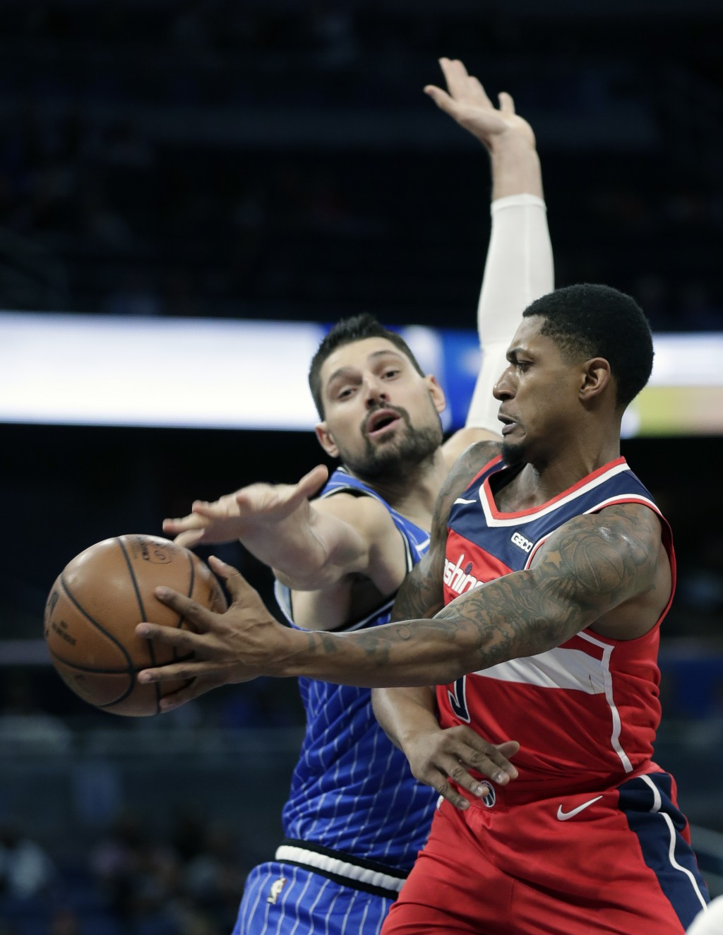 Washington Wizards' Bradley Beal, right, passes the ball around Orlando Magic's Nikola Vucevic during the first half of an NBA basketball game, Friday