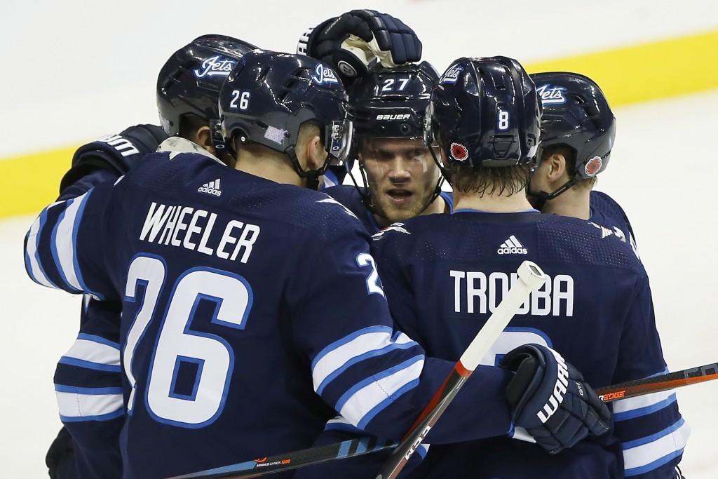 Winnipeg Jets' Mark Scheifele (55), Blake Wheeler (26), Nikolaj Ehlers (27), Jacob Trouba (8) and Josh Morrissey (44) celebrate Scheifele's goal durin