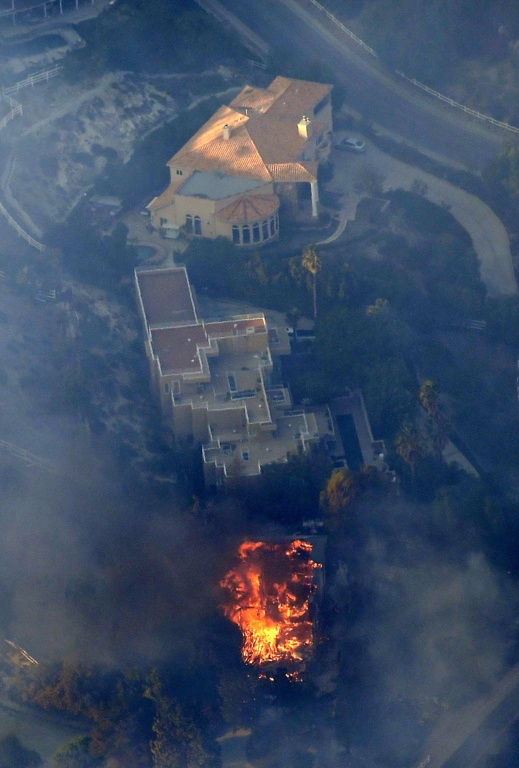 A home burns Friday, Nov. 9, 2018, as seen from a helicopter in the Calabasas section of Los Angeles. Flames driven by powerful winds torched dozens o