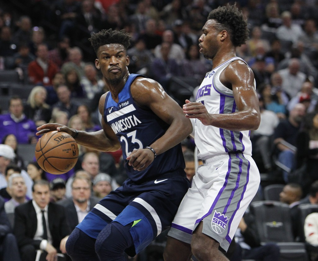 Minnesota Timberwolves guard Jimmy Butler (23) battles for position against Sacramento Kings guard Buddy Hield (24) during the first half of an NBA ba