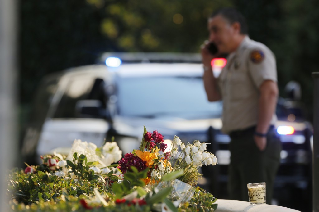 A bouquet of flowers, left by mourners, lays near the site of Wednesday's mass shooting, in Thousand Oaks, Calif., Friday, Nov. 9, 2018. Investigators