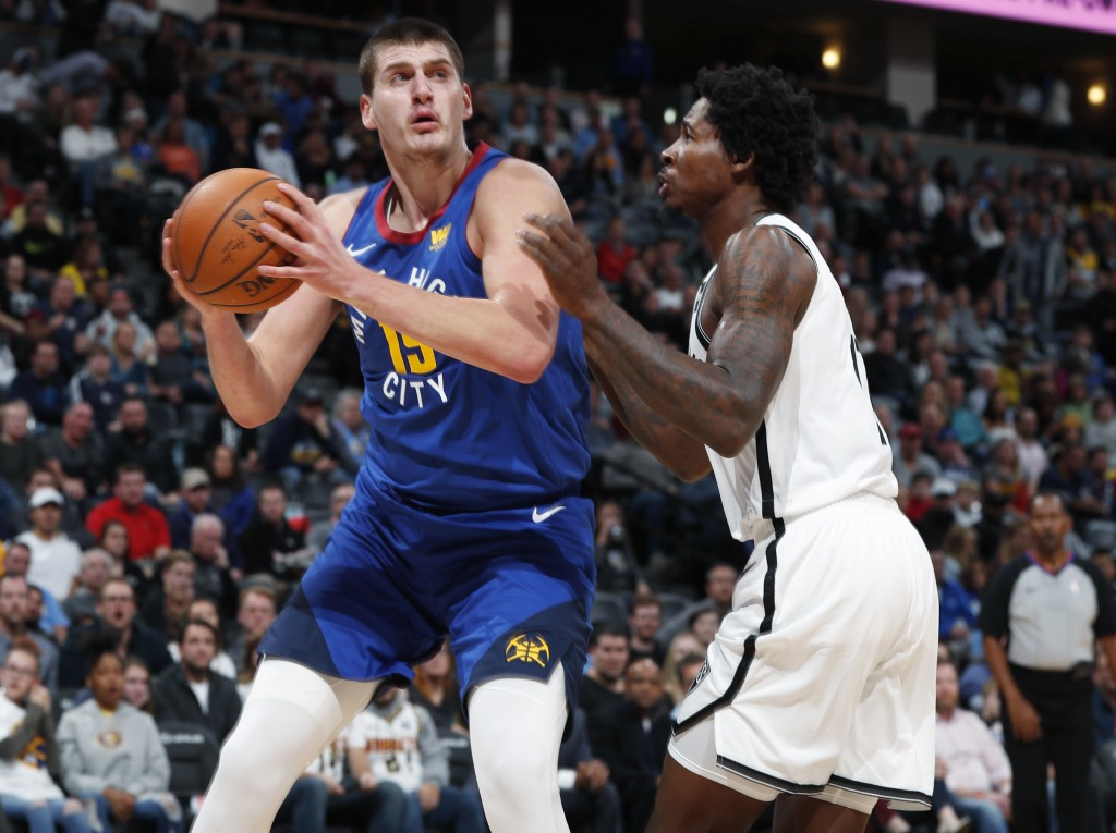 Denver Nuggets center Nikola Jokic, left, goes up for a basket as Brooklyn Nets forward Ed Davis defends in the first half of an NBA basketball game,