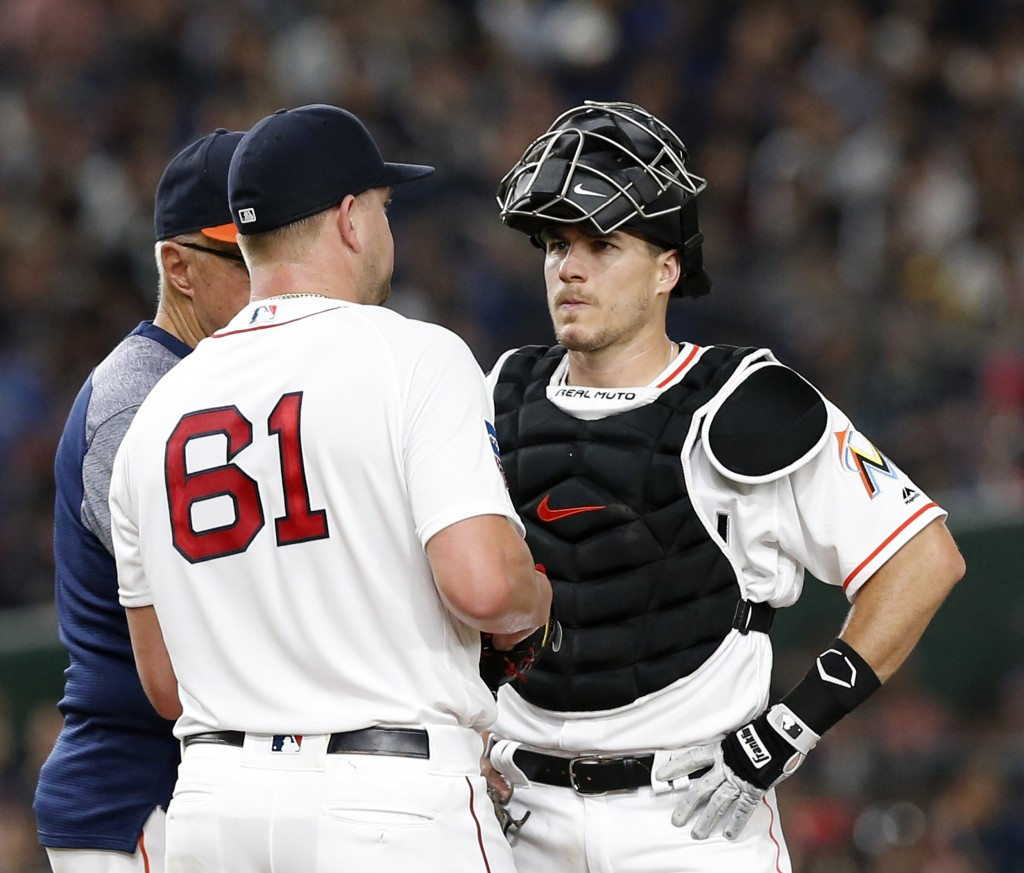MLB All-Star catcher J.T. Realmuto of the Miami Marlins talks with pitcher Brian Johnson (61) of the Boston Red Sox on the mound after giving up four