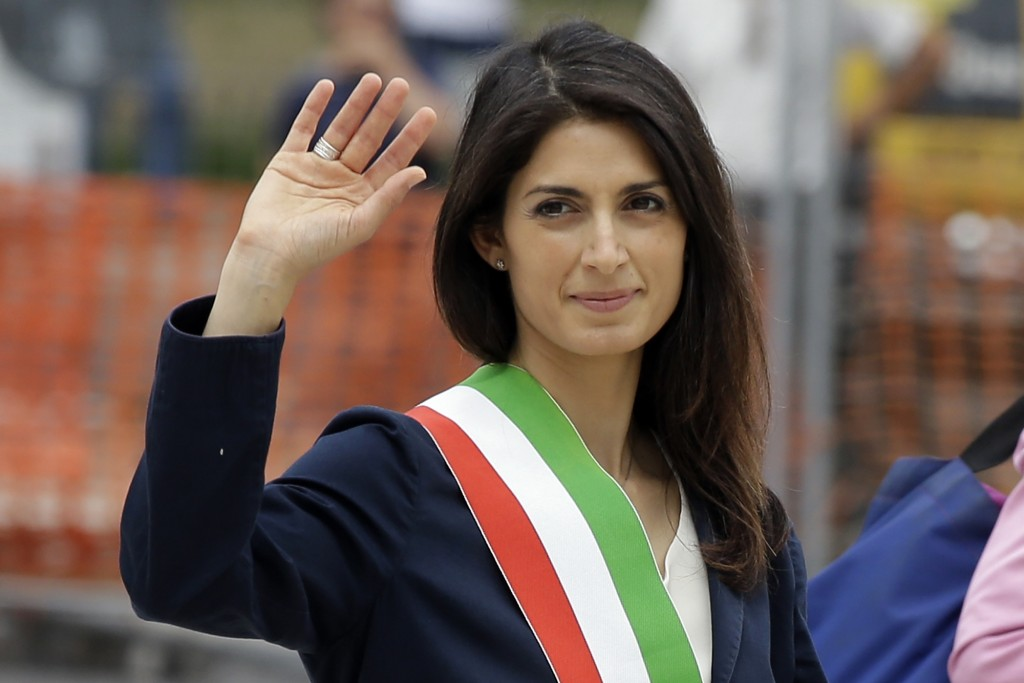 FILE - In this Thursday, June 23, 2016 file photo, Rome's Mayor Virginia Raggi waves to reporters in Rome. A verdict is nearing for Rome's mayor, on t