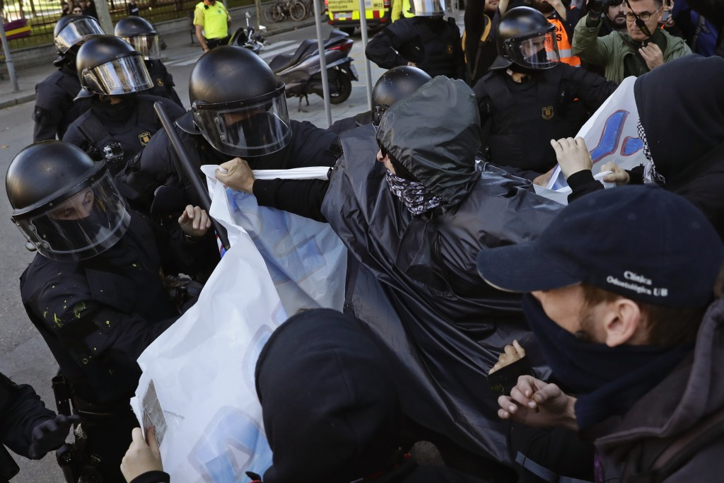 Police and protesters clash during a demonstration by CDR (Committees for the Defense of the Republic) in Barcelona, Spain, Saturday, Nov. 10, 2018. T
