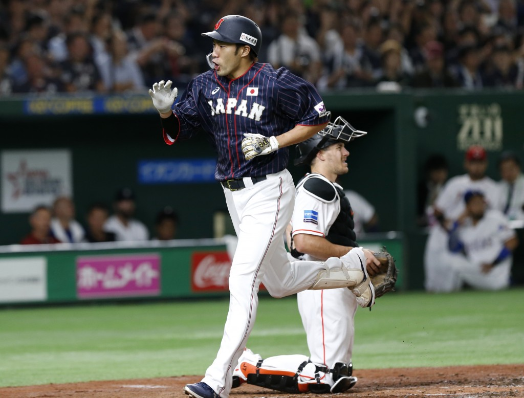 All Japan's designated hitter Yuki Yanagita crosses the plate past MLB All-Star catcher J.T. Realmuto of the Miami Marlins after hitting a two-run hom